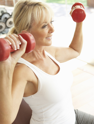 attractive woman performing a shoulder press with light dumbbells